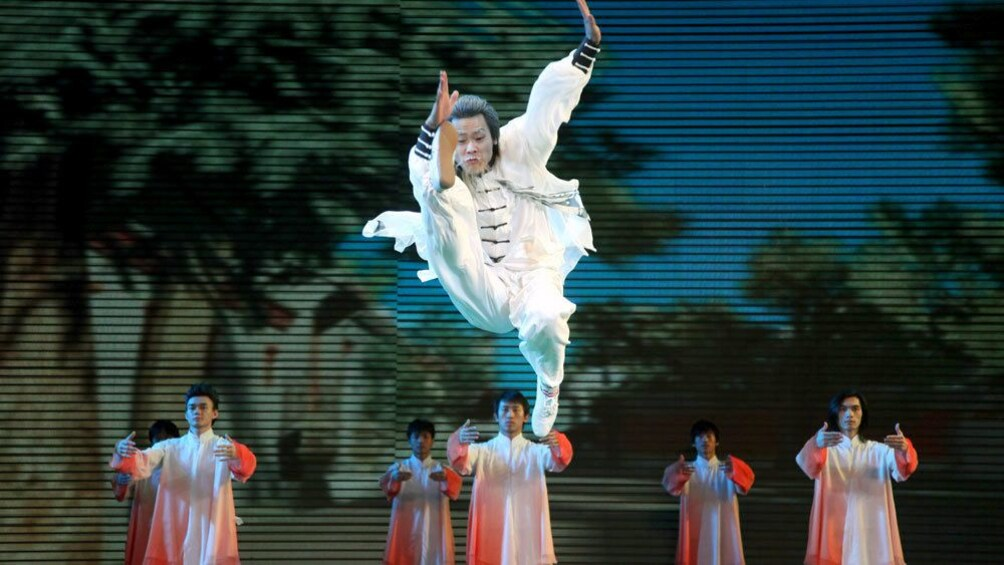 Show item 1 of 10. Man in white performing a jump kick in Beijing