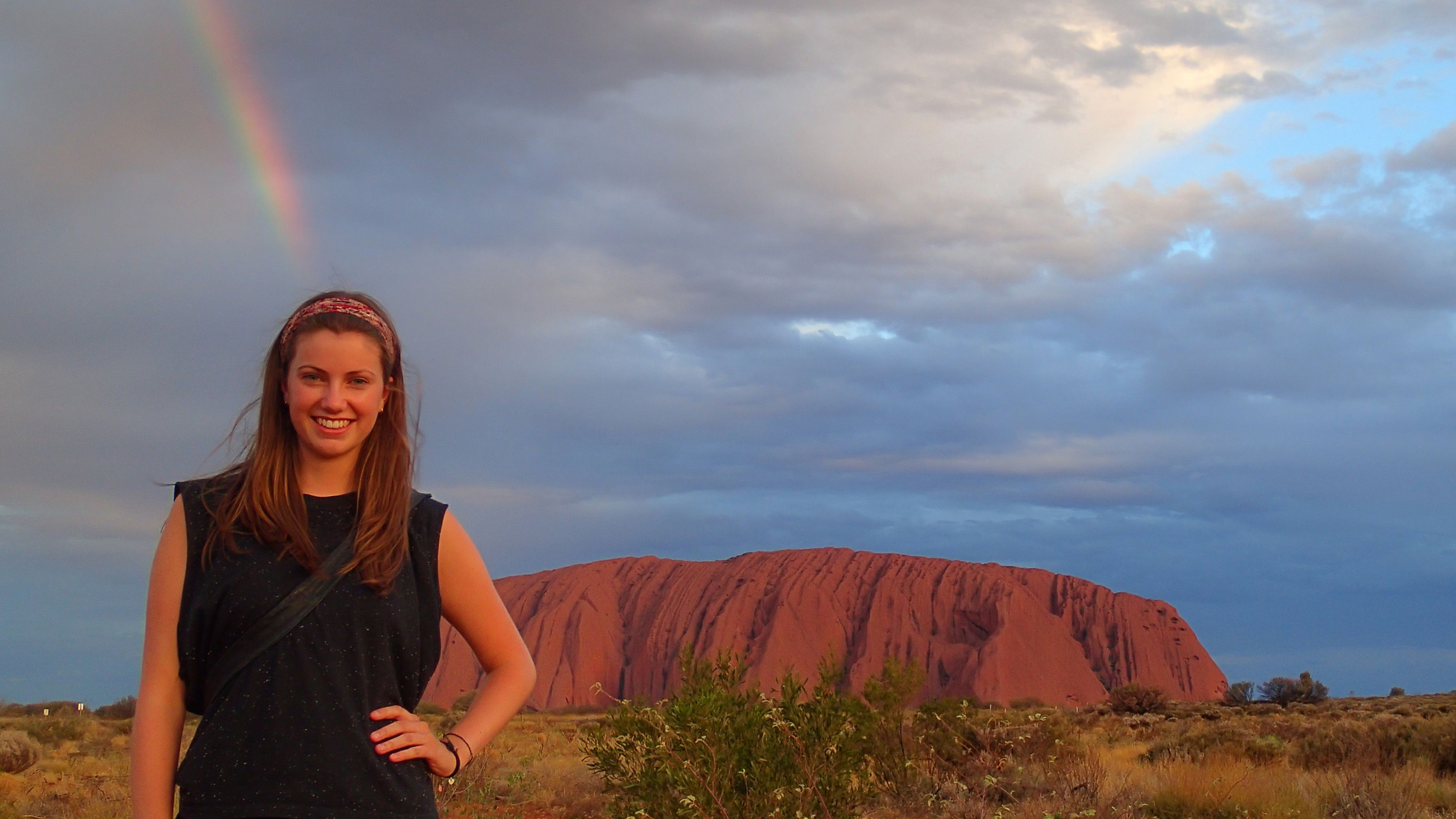 A woman infront of Ayers rock and a rainbow