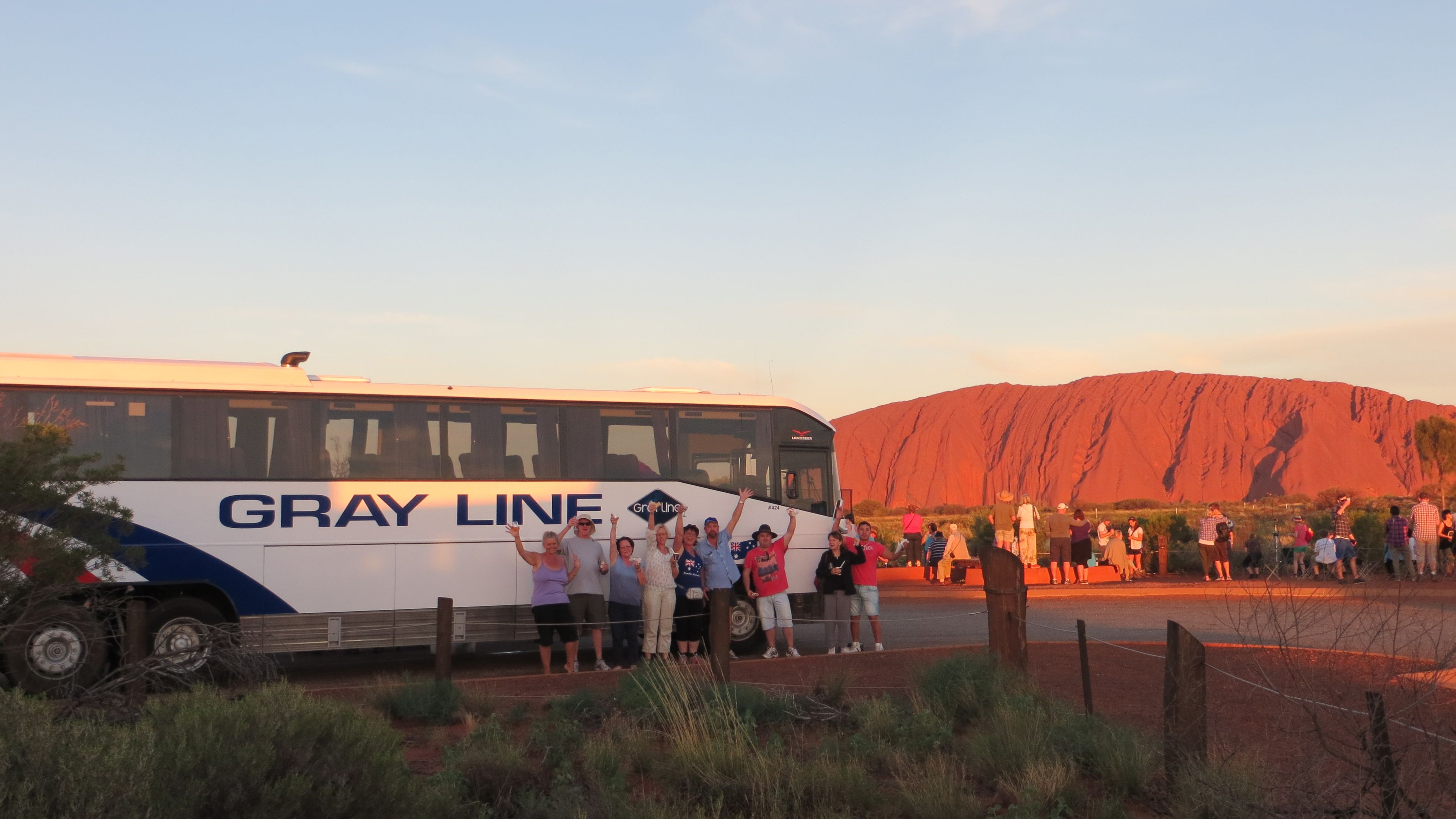 A tour bus and group near Uluru