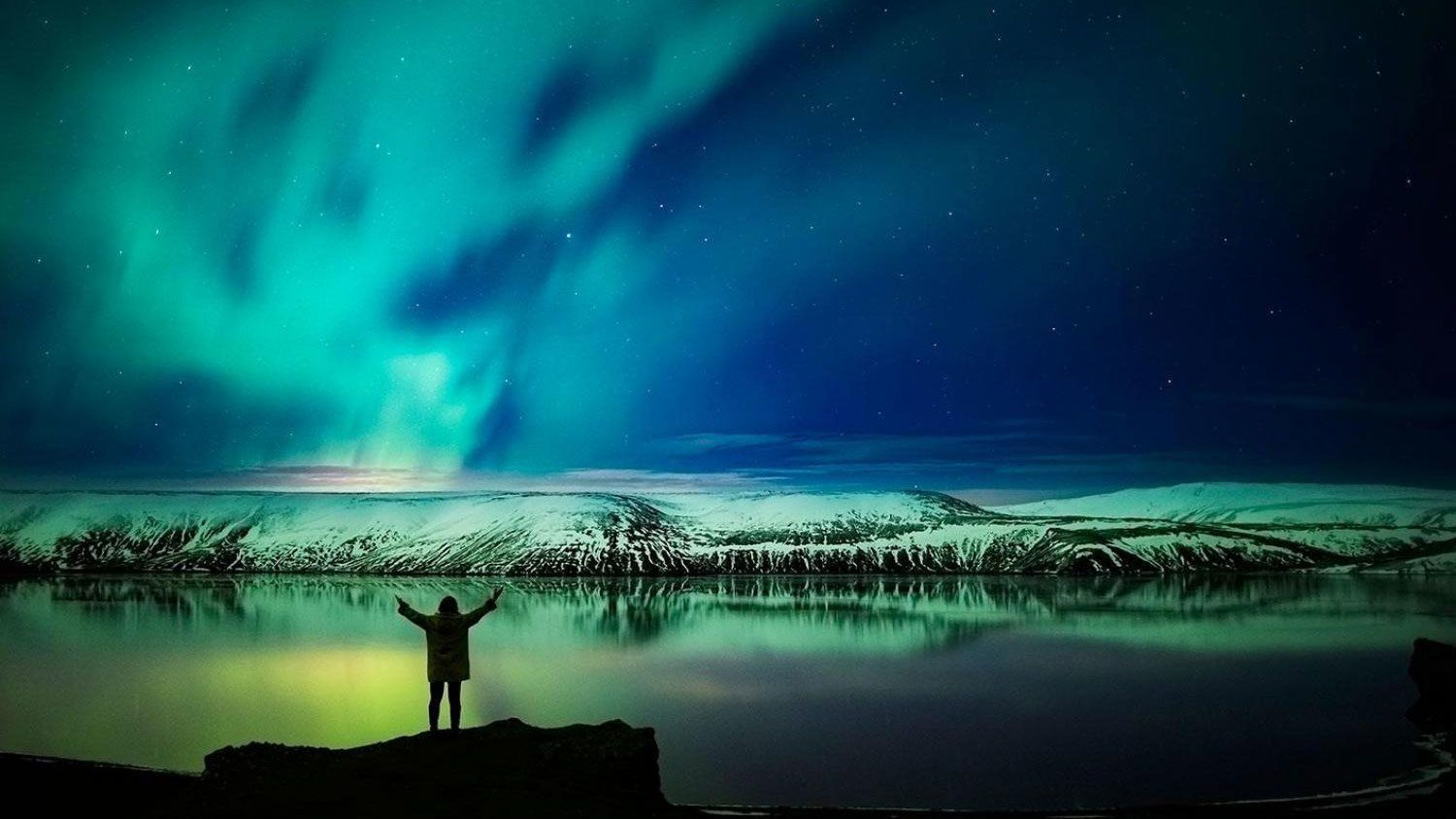 Woman with outstretched arms at edge of lake with Northern Lights above in Reykjavik