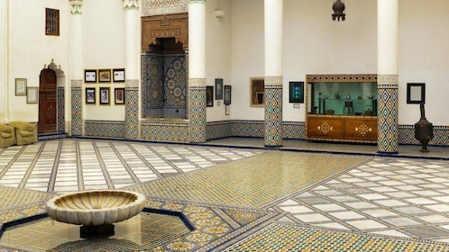 Artifacts on display among the colorful mosaic floor and pillars at the Museum of Moroccan Arts in Marrakesh