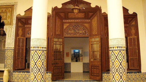 Mosaic pillars and large wooden doorway at the Marrakech Museum