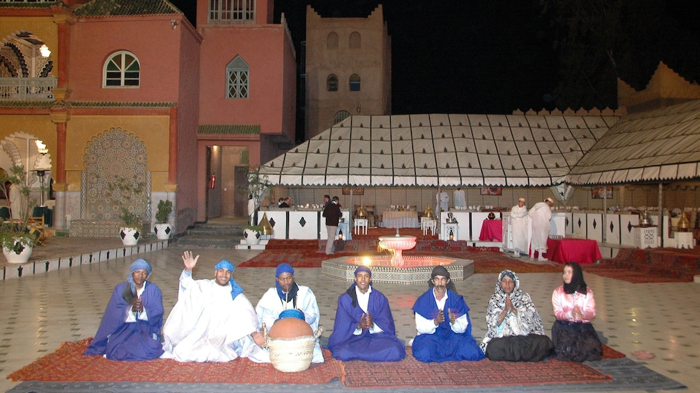 Seated performers in colorful robes during a performance in Marrakech
