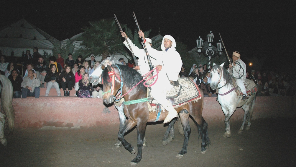 Riders with rifles on horseback during at night in Marrakech