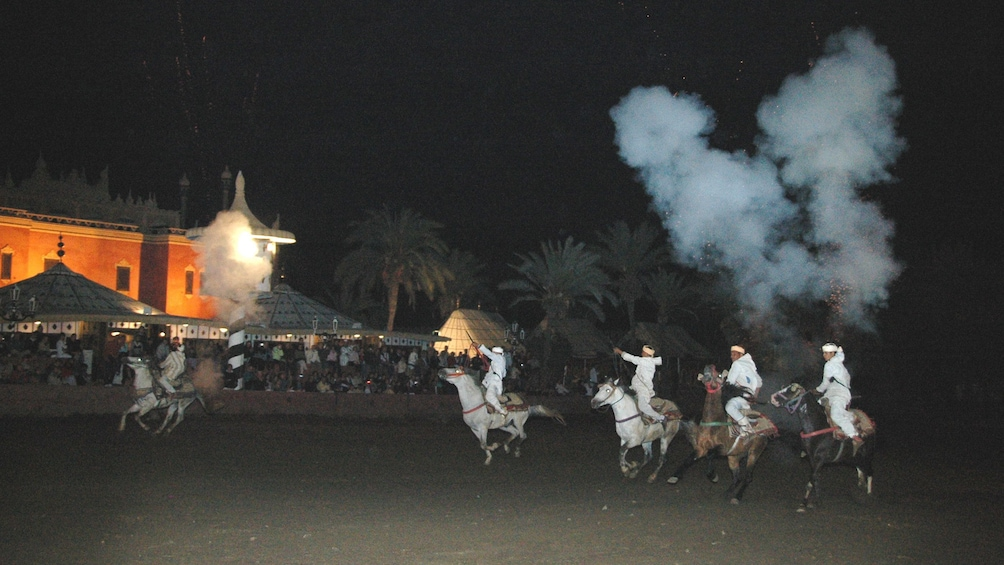 Horses and riders running during the Fantasia tribal horse charge at night in Marrakech