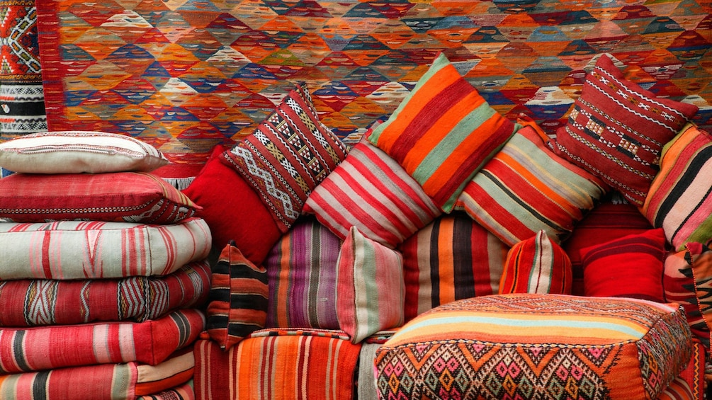 Charger l'élément 2 sur 7. Piles of colorful cushions and hanging rugs at a market in Ouarzazate