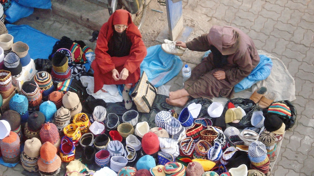 Vendors with handwoven crafts at a market in Marrakech