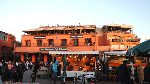 Fruit and vegetable stalls with restaurants behind at a market in Marrakech