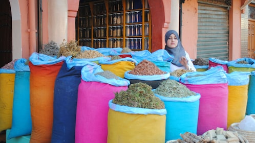 Market vendor with bins of herbs at a market in Marrakech