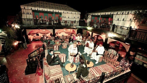 People enjoying beverages with live music outside at a restaurant in Marrakech