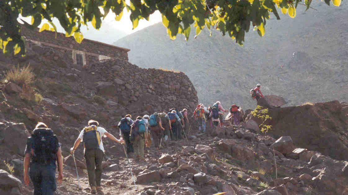 Atlas Mountain hiking group on a trail near a stone house in Marrakech