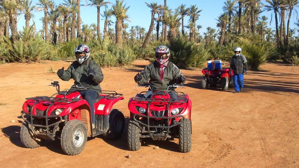 Apri foto 5 di 5. Quad-biking group with palm groves in the background in Marrakech