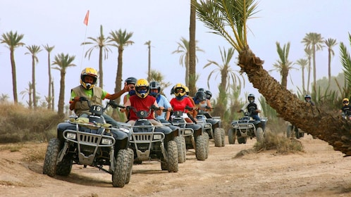 Quad-biking group on a dirt road lined with palm trees in Marrakech