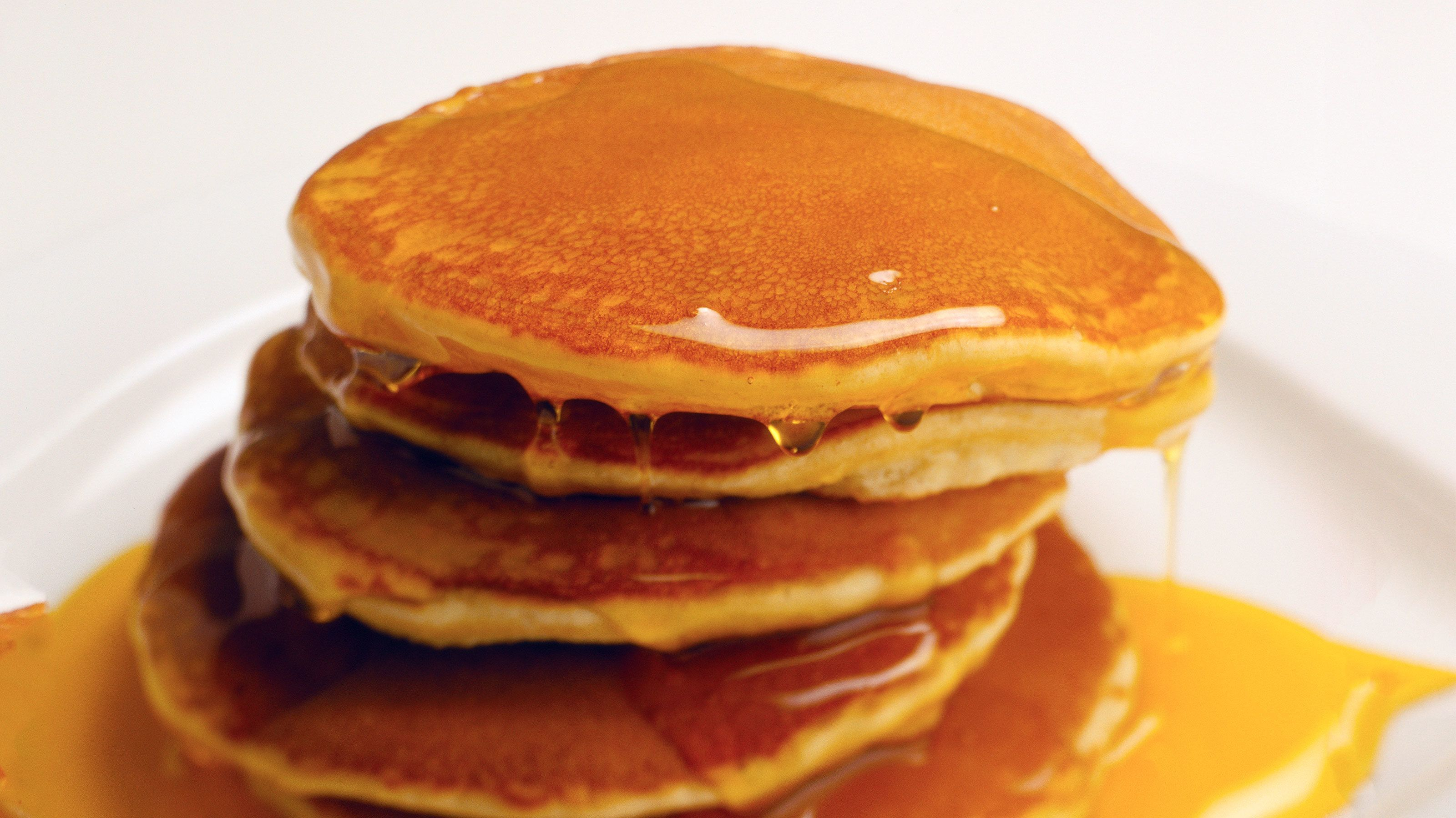 Stack of syrup-soaked pancakes on a plate.