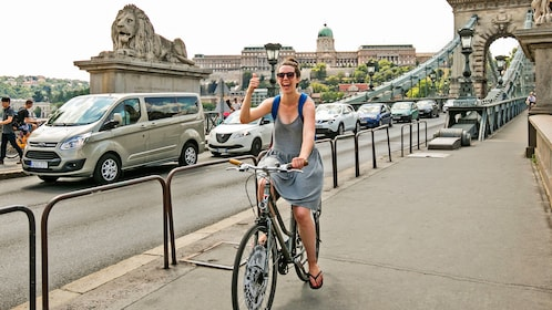 Woman on bike crosses bridge in Budapest