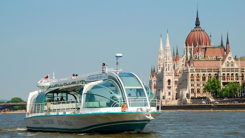 Beautiful view of the boat sailing on the Danube with a building in view in the distance