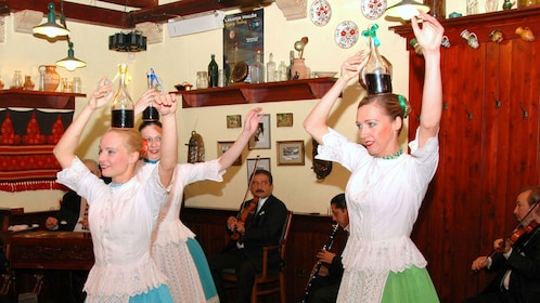 Ladies juggling a bottle on their heads while dancing at the Hungarian Folklore Show in Budapest