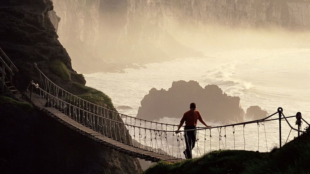 Charger l'élément 3 sur 10. man walking bridge above chasm at Giants Causeway in Dublim