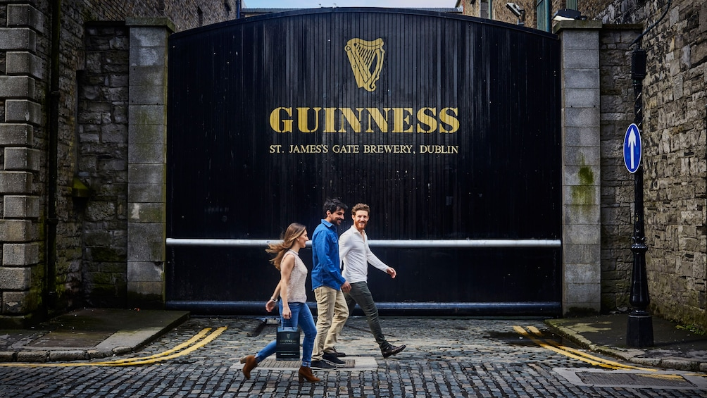 Show item 1 of 10. Three people walking in front of Guinness Brewery
