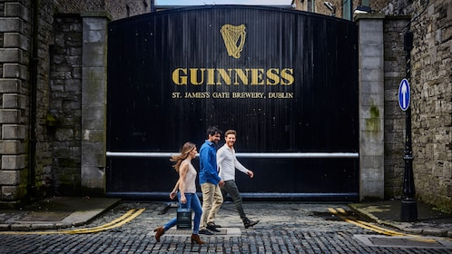 Three people walking in front of Guinness Brewery
