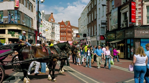 Clydesdale horses pulling a coach through crowded streets in Dublin
