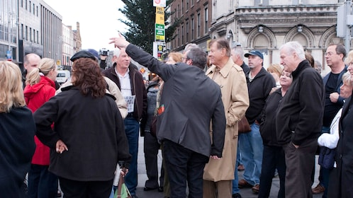 tour guide pointing out tourist attractions to a tour group in Dublin