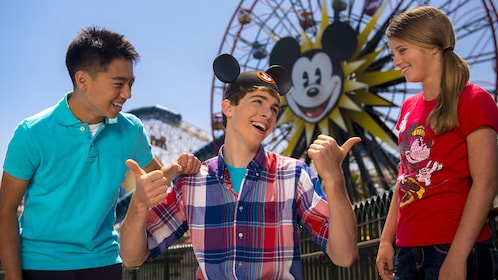 Young adult wearing Mickey Mouse ears and giving the thumbs up to two friends at Disneyland