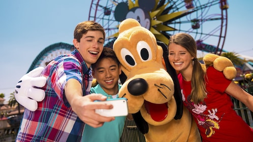 Three kids taking a photo with Pluto.