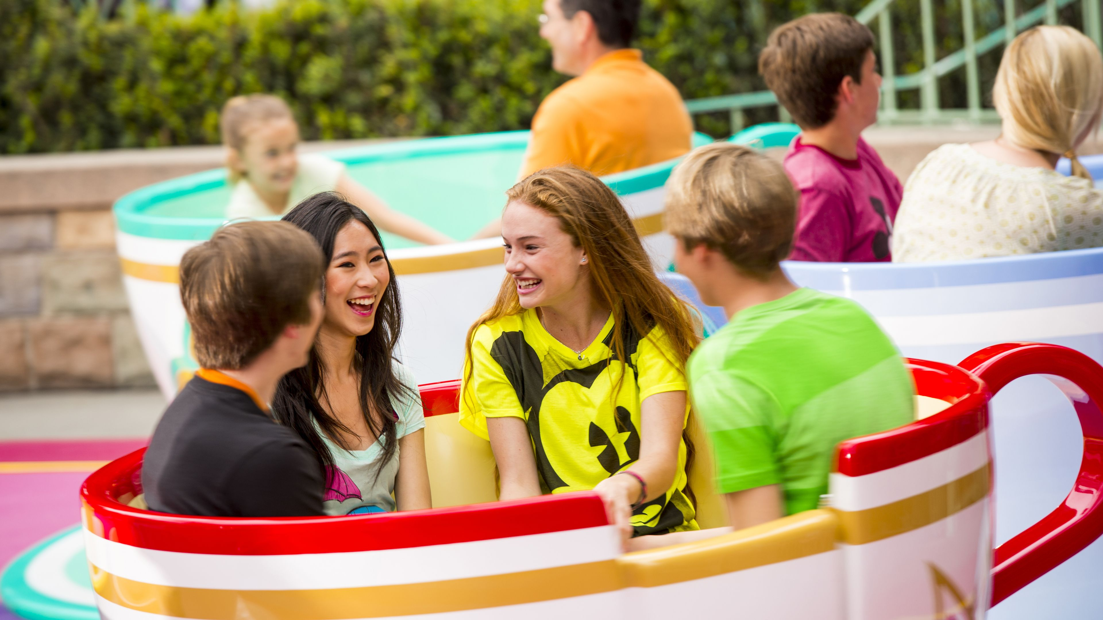 Four young adults in a teacup amusement ride at Disneyland