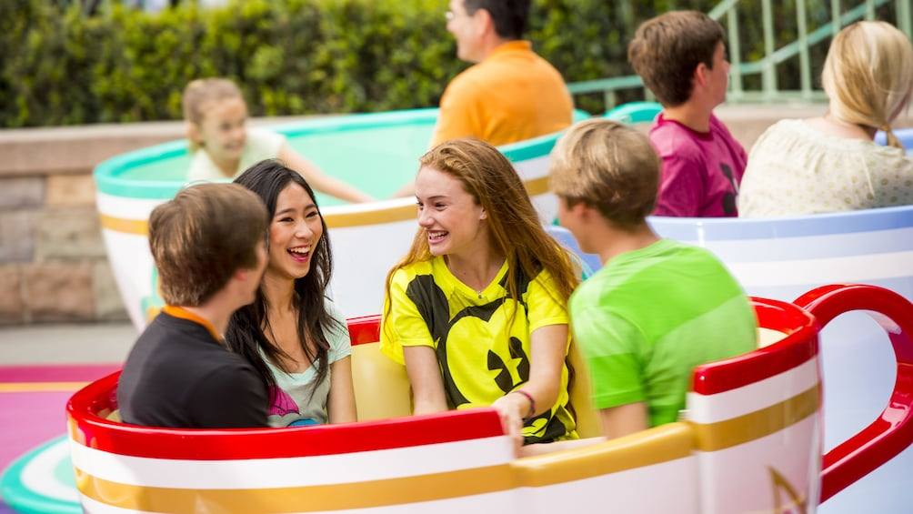 Show item 3 of 10. Four young adults  in a teacup amusement ride at Disneyland