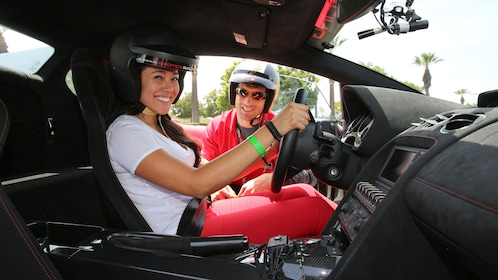 Driver and her instructor inside a Ferrari.