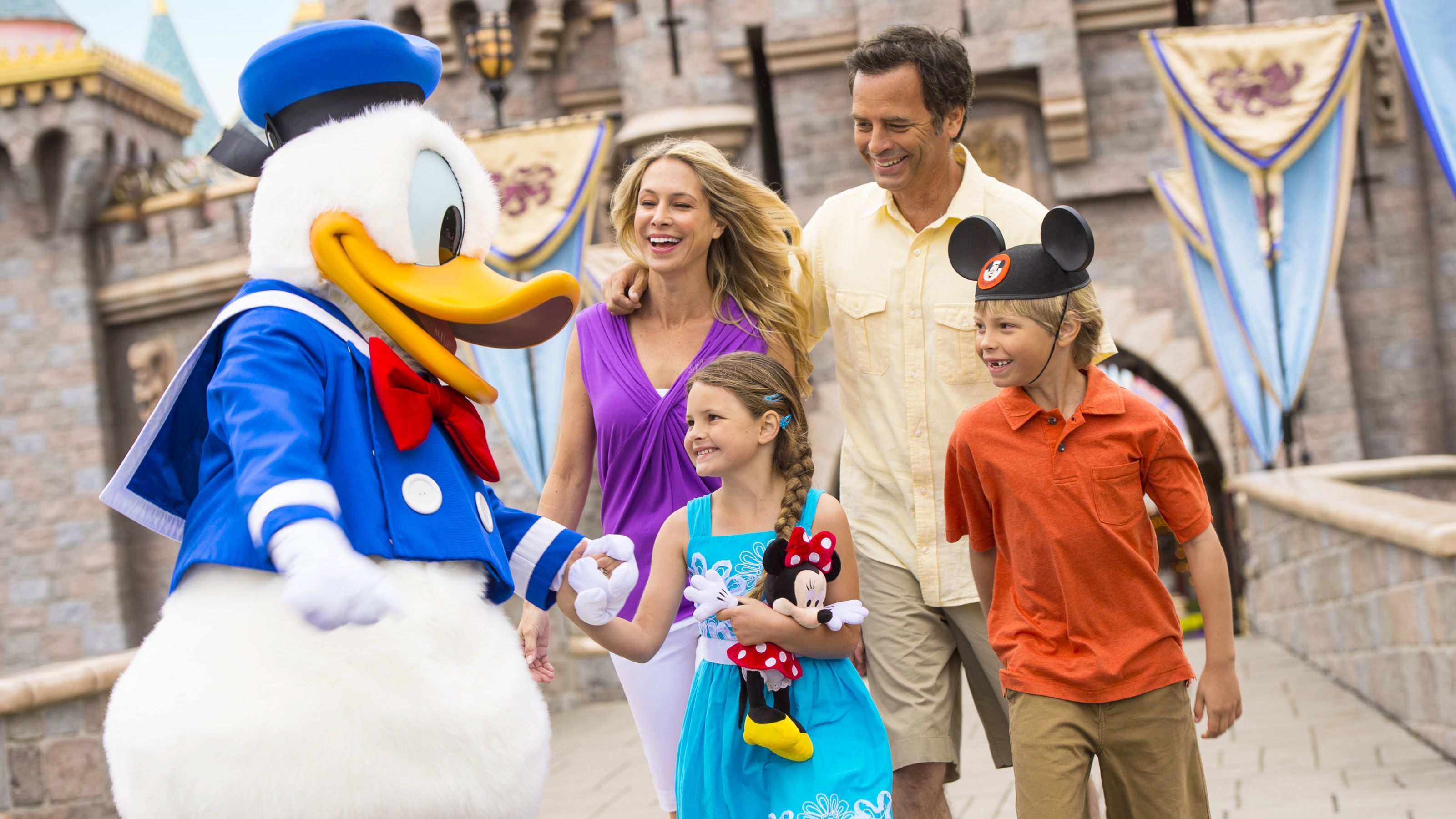 Happy family with Donald Duck in front of Sleeping Beauty's castle.