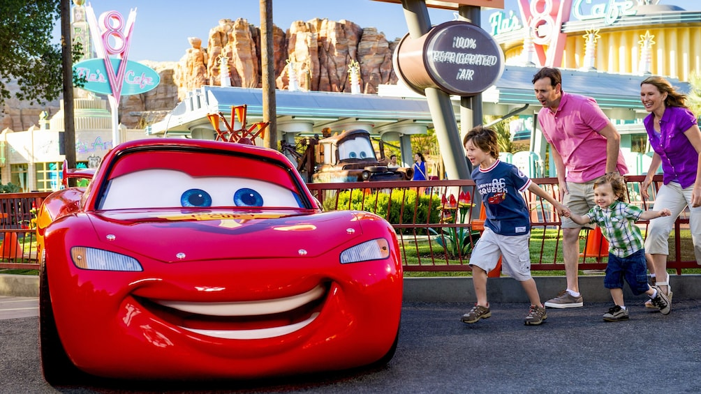 Show item 4 of 9. Lightning McQueen and a family in Radiator Springs, Disneyland