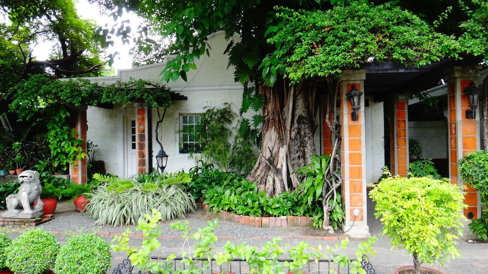 正在顯示第 1 張相片,共 10 張。 Colorful gardens outside an old house with tiled columns in Manila