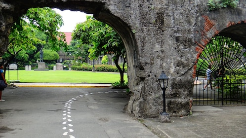 Road passing underneath old archway in Manila