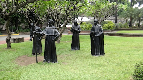 Statues of robes priests in a park in Manila