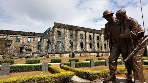 Statue of injured soldiers with ruins behind on Corregidor Island