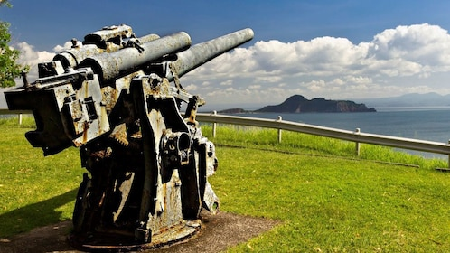 Old battery gun mounted on a hill pointed towards the water on Corregidor Island