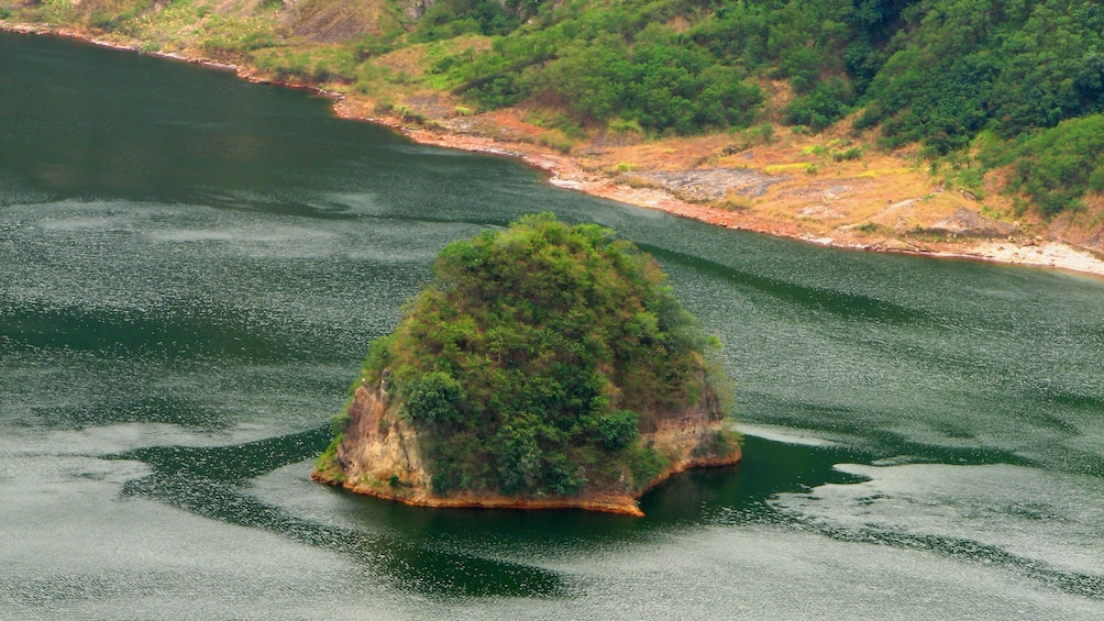 Show item 3 of 5. Tree covered rock island in Taal Lake in Tagaytay