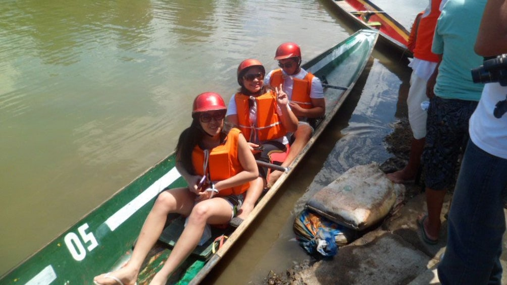 Show item 3 of 5. Group in a canoe on the river in Pagsanjan