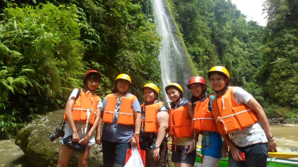 Group wearing lifejackets with Pagsanjan Falls in the background
