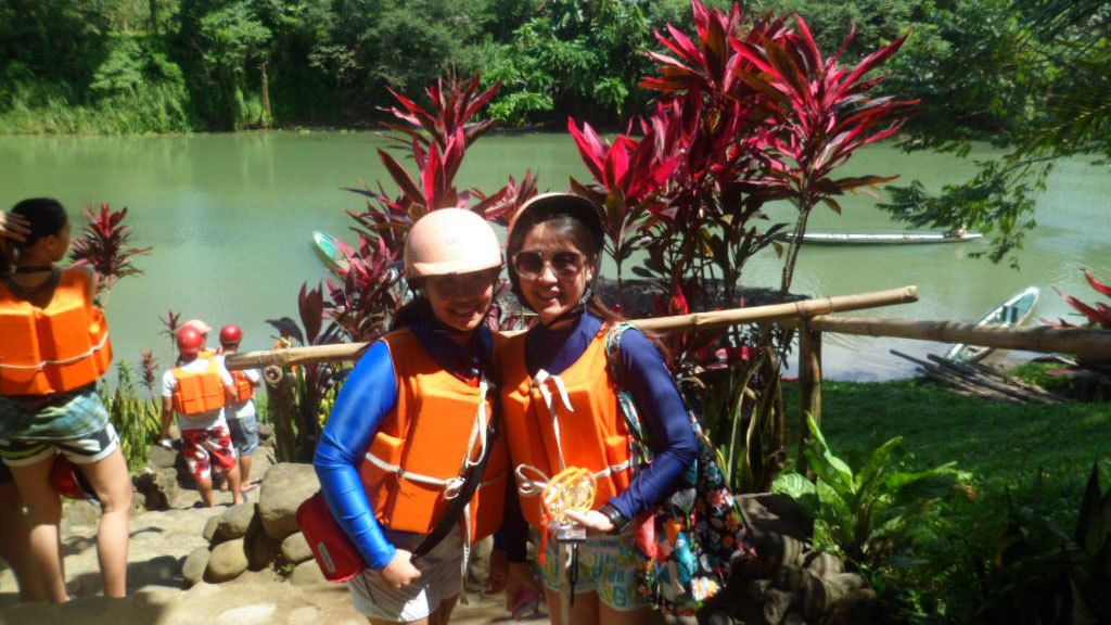 Pair of young women in lifejackets along the river in Pagsanjan