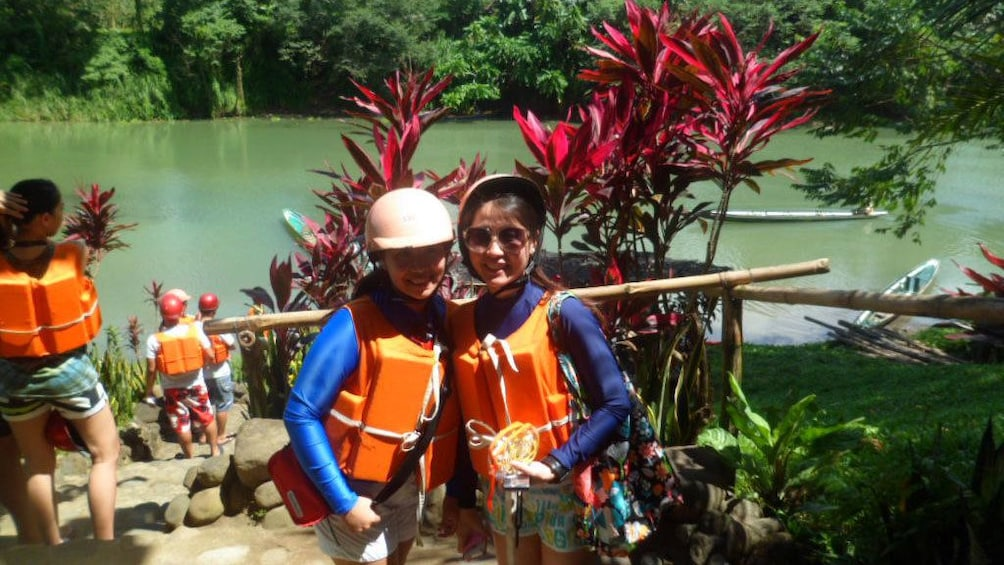 Show item 1 of 5. Pair of young women in lifejackets along the river in Pagsanjan