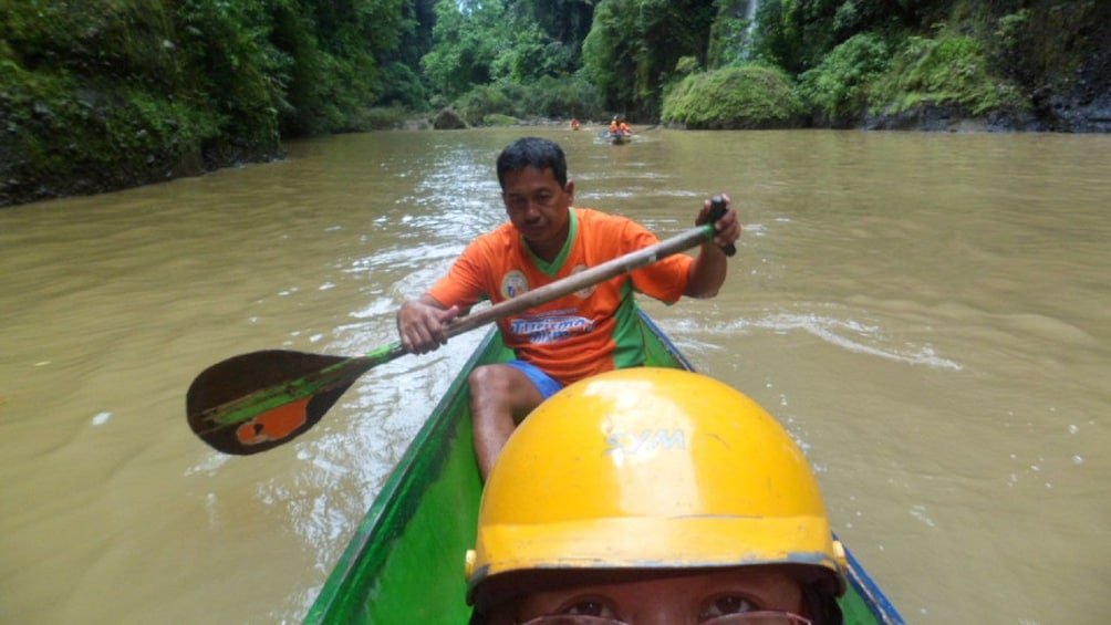 Show item 5 of 5. Canoe passengers travel down the river in Pagsanjan