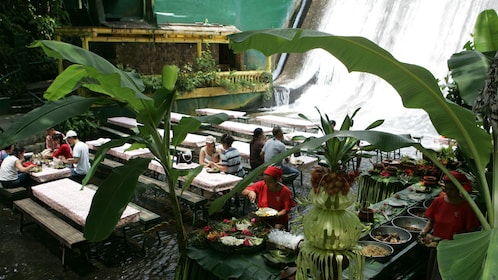 Dining tables at the bottom of a waterfall at Villa Escudero Plantations in San Pablo City, Philippines