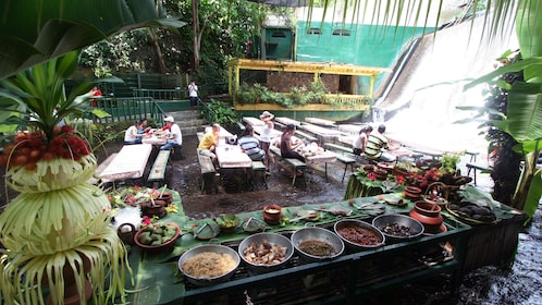 Bowls of prepared food and guests dining at the base of a waterfall at Villa Escudero Plantations in San Pablo City, Philippines