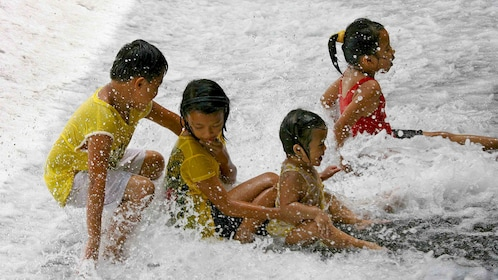 Group of children playing in the water at Villa Escudero Plantations in San Pablo City, Philippines