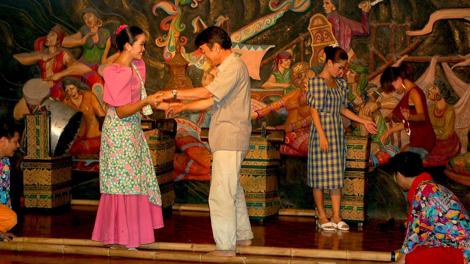Audience members are invited onstage to dance with the performers during a show in Manila