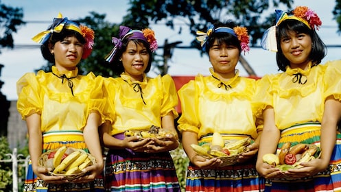 Young women in colorful costumes holding baskets of fruit in Manila