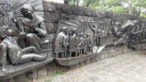 Metal sculptures along a stone wall in Manila
